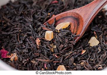 Dry tea leaves in wooden spoons