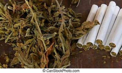 Dry tobacco leaves next to homemade cigarettes or roll-up...