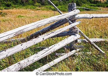 Dry wood log fence corner in long grass