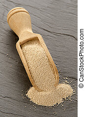 dry yeast on a wooden shovel