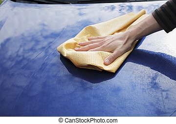 Drying car - A Hand drying a blue car with a synthetic...