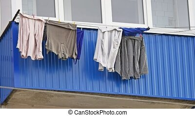 Drying clothes hanging on a balcony of the house