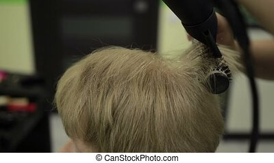 Drying female customer's hair with dryer and brush - Closeup...