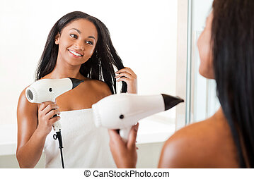 Drying hair in bathroom. Rear view of beautiful young African woman drying hair and smiling while standing in bathroom and against a mirror