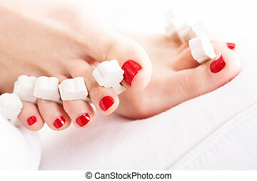 Drying nails - Close-up of female feet with red polished...