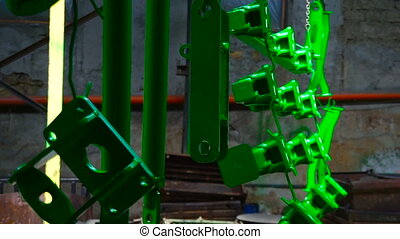 Drying rail in the factory with hanging green details of...
