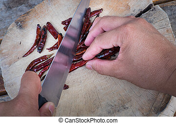 Drying the red hot chili pepper with knife on the chopping block