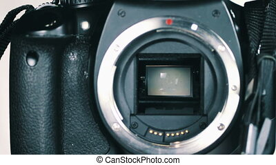 Moment of SLR of photographing, lifting mechanism mirror inside the camera and light strikes the CCD digital camera. Working Mechanism raising mirror a digital camera without Lenses. Close Up.