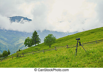 Dslr digital professional camera stand on tripod photographing mountain, Blue sky and cloud landscape.