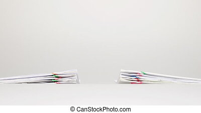 Dual pile overload document on white background time lapse -...