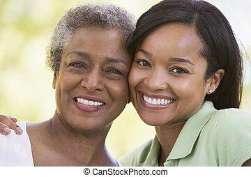 duas mulheres, ao ar livre, sorrindo