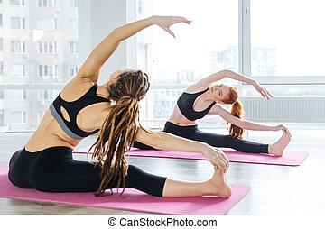duas mulheres, fazendo, esticar, exercícios, em, ioga, centro