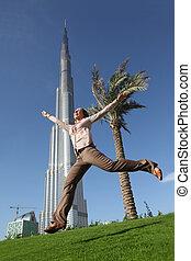 DUBAI - APRIL 17: Happy tourist woman in front of Burj Khalifa (Burj Dubai) , 17 april 2010 in Dubai, UAE. Emirat Dubai - the main tourist zone in the Near East.