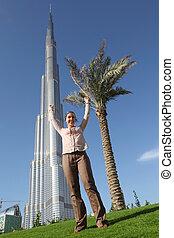 DUBAI - APRIL 17: Tourist woman stands in front of Burj Khalifa (Burj Dubai) , 17 april 2010 in Dubai, UAE. Emirat Dubai - the main tourist zone in the Near East.