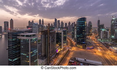 Dubai business bay towers day to night timelapse aerial -...