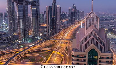 Dubai downtown skyline with tallest skyscrapers and busiest traffic on highway intersection night to day timelapse