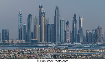 Dubai Marina skyline day to night timelapse as seen from atlantis on  Palm Jumeirah in Dubai, UAE.