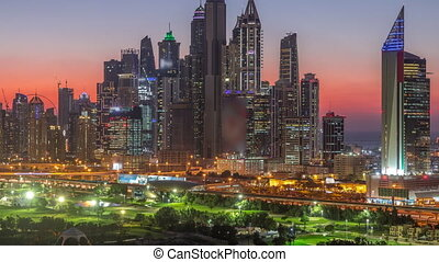 Dubai Marina skyscrapers and golf course day to night transition timelapse, Dubai, United Arab Emirates. Aerial view from Greens district after sunset