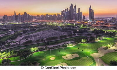 Jumeirah lake towers and Dubai Marina skyscrapers and golf course day to night transition timelapse, Dubai, United Arab Emirates. Aerial view from Greens district after sunset