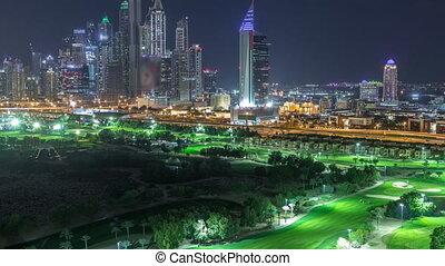 Dubai Marina skyscrapers and golf course night timelapse,...