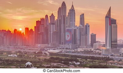 Dubai Marina skyscrapers and golf course sunset timelapse, Dubai, United Arab Emirates. Aerial view from Greens district. Rays of light and orange sky