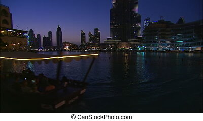 Medium low-angle dawn still shot from water, of Dubai Opera building, and other downtown skyscrapers, Dubai, UAE