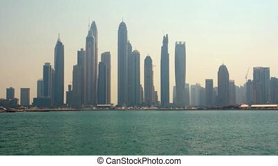 Cityscape of Dubai with modern, highrise architecture, towering over the sea in the late afternoon sun. UltraHD 4k footage