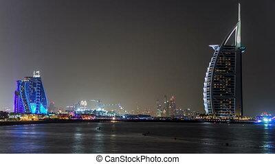 Dubai skyline with Burj Al Arab hotel at night timelapse.
