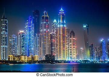 DUBAI, UAE - NOVEMBER 13: Dubai downtown night scene with city lights, luxury new high tech town in United Arab Emirates architecture on November 13, 2012 in Dubai, UAE. Dubai Marina cityscape, UAE