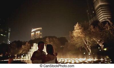 DUBAI, UAE - NOVEMBER 13: The girl and the guy dance near night fountain in Dubai on November 13, 2015 in Dubai, UAE
