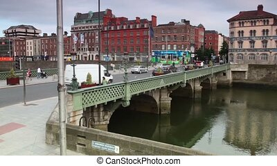 Cars and passers-by cross the Grattan bridge over the river Liffey