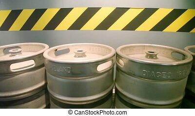Kegs of beer stands on moving conveyor belt in  factory