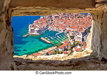 Dubrovnik historic city and harbor aerial view through stone window from Srd hill,