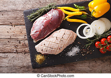 duck breast raw, with vegetables and spices close-up on a...