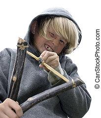 Close-up of boy with slingshot