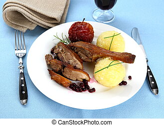 Duck leg with potato dumplings, red apple and cranberries