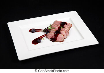 duck meat with cranberry cream in white plate on a black ...