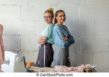 due, carino, giovane, femmina, progettista, guardando macchina fotografica, in, cucito, workshop.