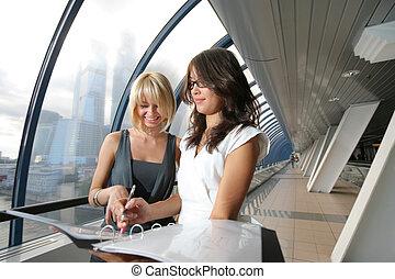 due, donne affari, guardando, carte, in, futuristico, interno