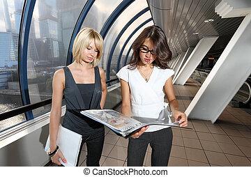 due, donne affari, guardando, cartella, in, futuristico, interno