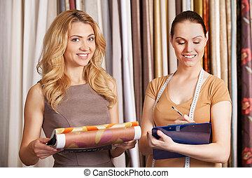 due, giovani donne, standing, in, store., bello, ragazza, selezione, tessuto, e, sorridente