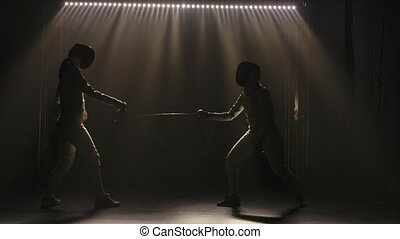 Duel of two female fencers. Professional fencers rivals demonstrate mastery of foil fencing. Black smoky background with backlit lights. Slow motion