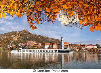 DUERNSTEIN CASTLE AND VILLAGE WITH BOAT ON DANUBE RIVER DURING AUTUMN TIME IN AUSTRIA