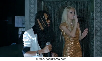 Duet African American man and a blonde woman singing. Slow motion