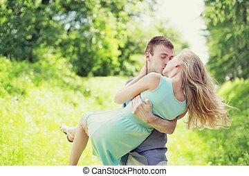 dulce, beso, pareja joven, aire libre, hombre y mujer, enamorado, él, asideros, ella, en, un, manos, en, pasto o césped