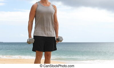 Dumbbell Bicep Curl exercise - fitness man exercising arms on beach. Unrecognizable fit sport fitness model showing correct technique on classic weight lifting workout exercise. REAL TIME.
