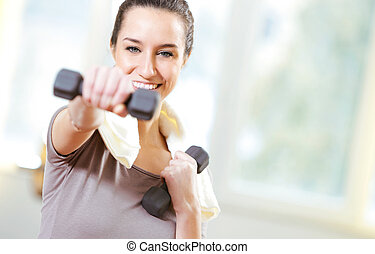dumbbell in hand of working out young smiling female