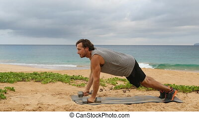 Dumbbell Plank Row. Fitness man doing Alternating Renegade Row exercise using dumbbells while exercising outside on beach.