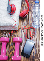 dumbbells and a bottle of water with towel on wooden background, concept preparing to fitness sports equipment top view. Headphones and phone. Music in sports.