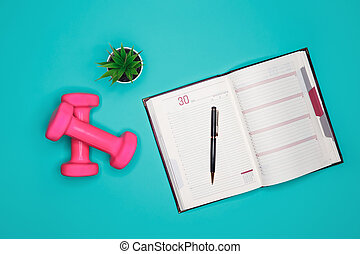 On a turquoise background are pink dumbbells, a houseplant and a diary with a pen for recording the training regime, proper nutrition, physical activity and water balance